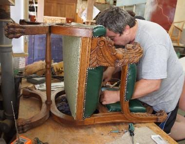 Обивка старинного резного кресла из дуба кожей. Линии соединения деревянного каркаса и кожаной обивки декорированы металлическим сайдингом в виде сплошного ряда мебельных гвоздиков.